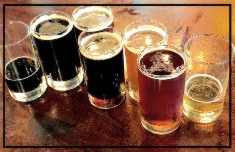 Seven taster glasses of beer.